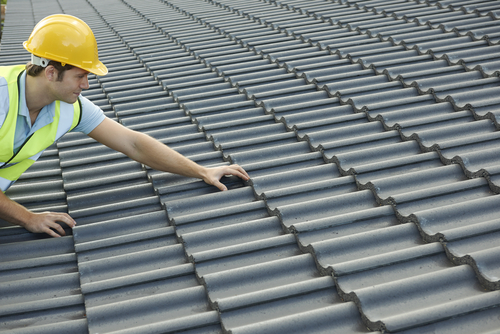 construction worker adjusting roof tile