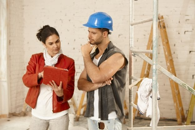 Woman in suit showing construction worker item on ipad